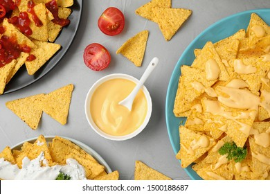 Mexican nacho chips with different sauces on grey table, flat lay