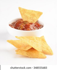 Mexican nacho chips and salsa dip in white bowl