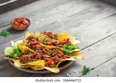 Mexican nacho corn tortilla chips with  meat and red hot spicy salsa. Nachos with ground beef on wooden background, copy space.