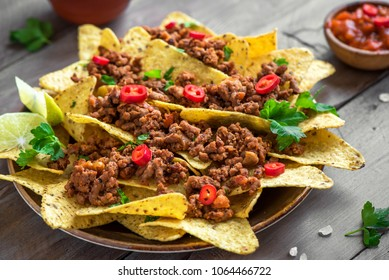 Mexican nacho corn tortilla chips with  meat and red hot spicy salsa. Nachos with ground beef on wooden background.
