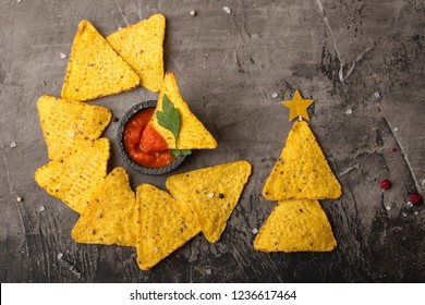 Mexican nacho tortilla tortilla with cheese and sauce. The concept of the new year from the Mexican nachos. Christmas trees from nacho chips on a dark background. View from above. Copy space