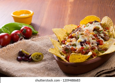 Mexican Nachos baked in casserole with cheese, beans, corn, hot jalapeno, chicken, red pepper and mushrooms serving on wood table.