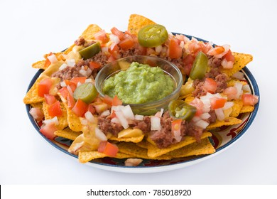 Mexican nachos with beef, guacamole, cheese sauce, peppers, tomato and onion in plate isolated on white background