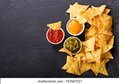 mexican nachos corn chips with guacamole, salsa and cheese dip on dark background