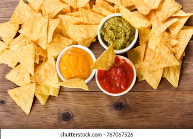 mexican nachos corn chips with guacamole, salsa and cheese dip on wooden table