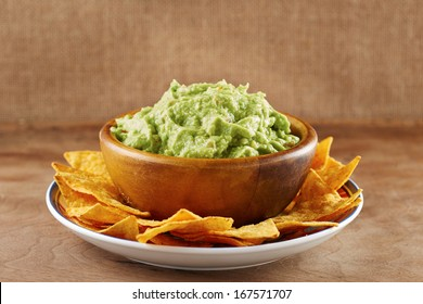 Mexican nachos with handmade guacamole sauce on wooden table