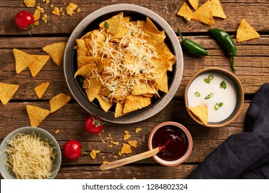 Mexican nachos served with cheese, variety of dips, chilly, tomatoes on a rustic wooden table