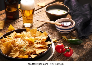 Mexican nachos served with cheese, variety of dips, beer, chilly, tomatoes on a rustic wooden table