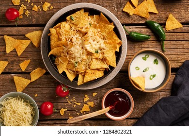 Mexican nachos served with melting cheese, variety of dips, chilly, tomatoes on a rustic wooden table