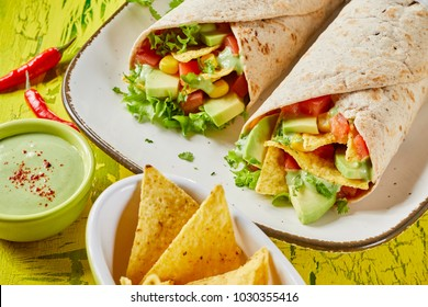Mexican nachos torilla wraps with avocado pear and salad trimmings served with guacamole dip and chips