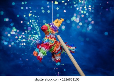 mexican piñata party hanging on blue and green background with multi-colored glitters celebrating birthday, christmas, party, party songs, figure in the shape of star and donkey, family fun