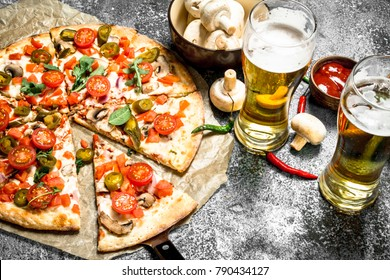 Mexican pizza with cold beer. On a rustic background.