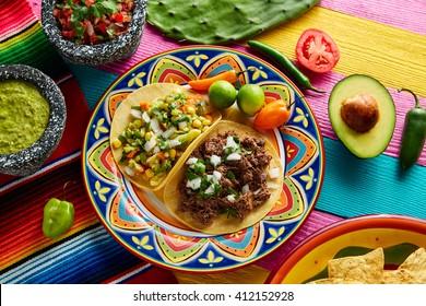 mexikanische Platillo-Takos von Barbacoa und vegetarisch mit Soßen und bunten Tisch