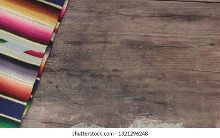 Mexican poncho serape background fiesta cinco de mayo wooden copy space stripe pattern. Sarape, traditional crafts from Saltillo, Mexico.