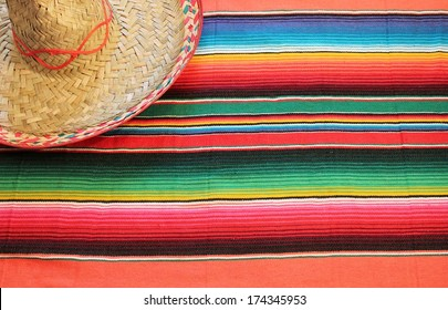 Mexican poncho sombrero background fiesta serape Mexico blanket rug in bright colours with copy space cinco de mayo flat lay minimal minimalist pattern