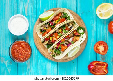 Mexican pork tacos with vegetables. Tacos al pastor on wooden blue rustic background. Top view