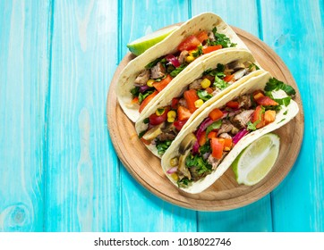 Mexican pork tacos with vegetables on wooden blue rustic background.