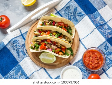 Mexican pork tacos with vegetables on wooden blue rustic background