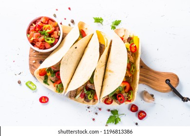 Mexican pork tacos with vegetables and salsa. Traditional Latin american food. Top view on white.