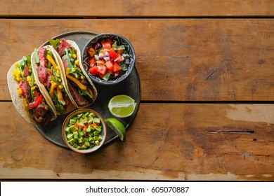 Mexican pork tacos with vegetables and salsa. Tacos al pastor on wooden rustic background. Top view, flat, overhead. Copy space and text area.