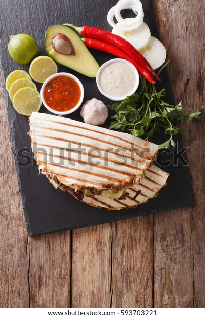 Mexican quesadilla with beef, beans, avocado and cheese close-up on the table. vertical view from above
