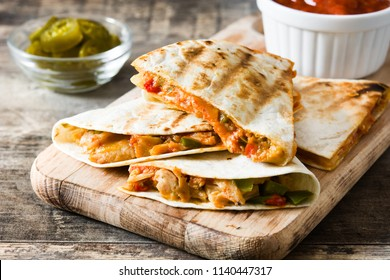Mexican quesadilla with chicken, cheese and peppers on wooden table.
