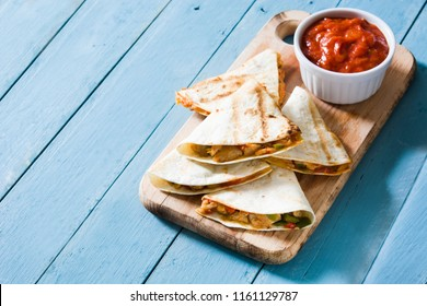 Mexican quesadilla with chicken, cheese and peppers on blue wooden table. Copyspace