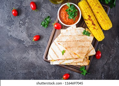 Mexican Quesadilla wrap with chicken, corn and sweet pepper and tomato sauce. Top view. Flat lay