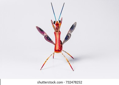 Mexican red mantis alebrije isolated in white background in front view