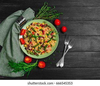 Mexican rice with vegetables. Ingredients for Mexican rice are beans, corn kernels, peppers, cherry tomatoes, rucola salad, thyme. Dark black wooden background. Top view. Blank space.