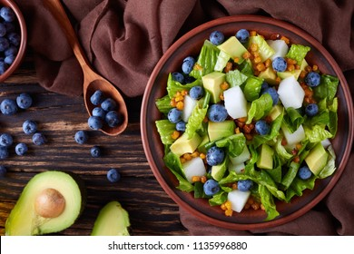 Mexican Salad with Blueberries, romaine lettuce leaves, jicama, roasted crispy Corn kernels and Avocado on a plate on an old rustic wooden table with ingredients, view from above, close-up, flatlay