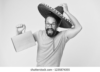 Mexican shopping. Man smiling face in sombrero hat shopping yellow background. Guy with beard looks festive in sombrero. Holiday sales concept. Man in festive mood shopping traditional sales season.