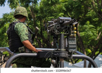 Mexican soldier carring heavy weaponry in a militar truck holding a grenade launcher with bullets showing up