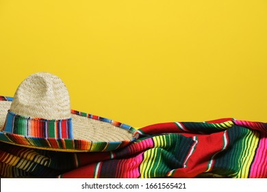 Mexican sombrero on a colorful serape blanket on a yellow background. Cinco de Mayo theme