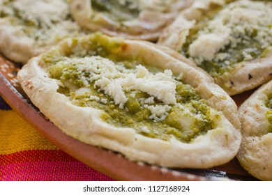 Mexican sopes with grated cheese and green salsa, mexican food spicy in mexico