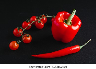 Mexican spicy food is on plate, and next to it are red hot peppers and cherry tomatoes.