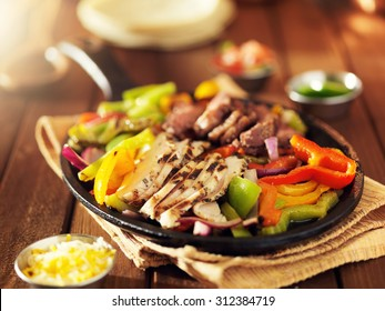 mexican steak and chicken fajitas in iron skillet with bell peppers and onion shot with warm colored light