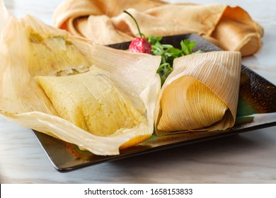 Mexican steamed chili and cheese masa tamales wrapped in corn husk