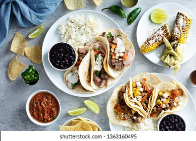Mexican street food variety with tacos, grilled corn. chips and salsa
