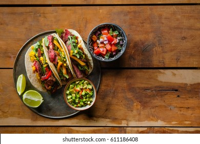 Mexican street tacos flat lay composition with pork carnitas, avocado, onion, cilantro, and red cabbage. Flat top view.