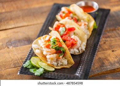 Mexican Street Tacos With Shrimp, Rice And Salsa In Yellow Corn Tortilla On Distressed Wood Table Selective Focus.