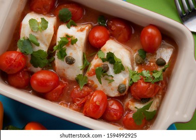 Mexican style baked cod with cherry tomatoes. Garnished with mexican condiments: guacamole, spicy salsa, marinated hot pepper, grilled corn, tortilla chips, and glass of beer.