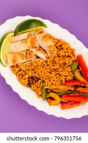 Mexican Style Chicken With Spicy Rice and Fried Peppers Against A Purple Background