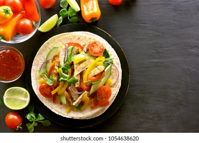 Mexican taco with chicken meat and vegetables on black stone background with copy space. Top view, flat lay