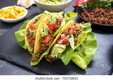mexican taco corn shells stuffed with fried ground beef, tomato salsa and guacamole on a dark slate plate, selected focus, narrow depth of field