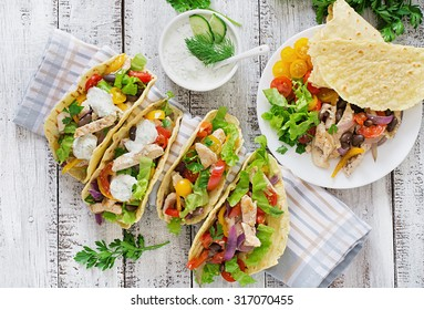 Mexican tacos with chicken, bell peppers, black beans and fresh vegetables and tartar sauce. Top view