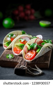 Mexican tacos with fresh vegetables and lime on concrete table