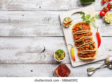 Mexican tacos with ground beef, beans and salsa on cutting board over wooden background. Top view