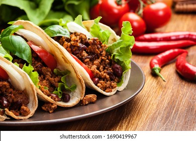 Mexican tacos with minced meat, beans and spices on a plate
