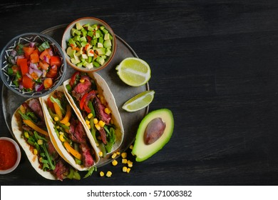 Mexican tacos - traditional dish with ingredients meat and vegetables on the plate on a black wooden background, top view. Black background for text and design. Flat top view.